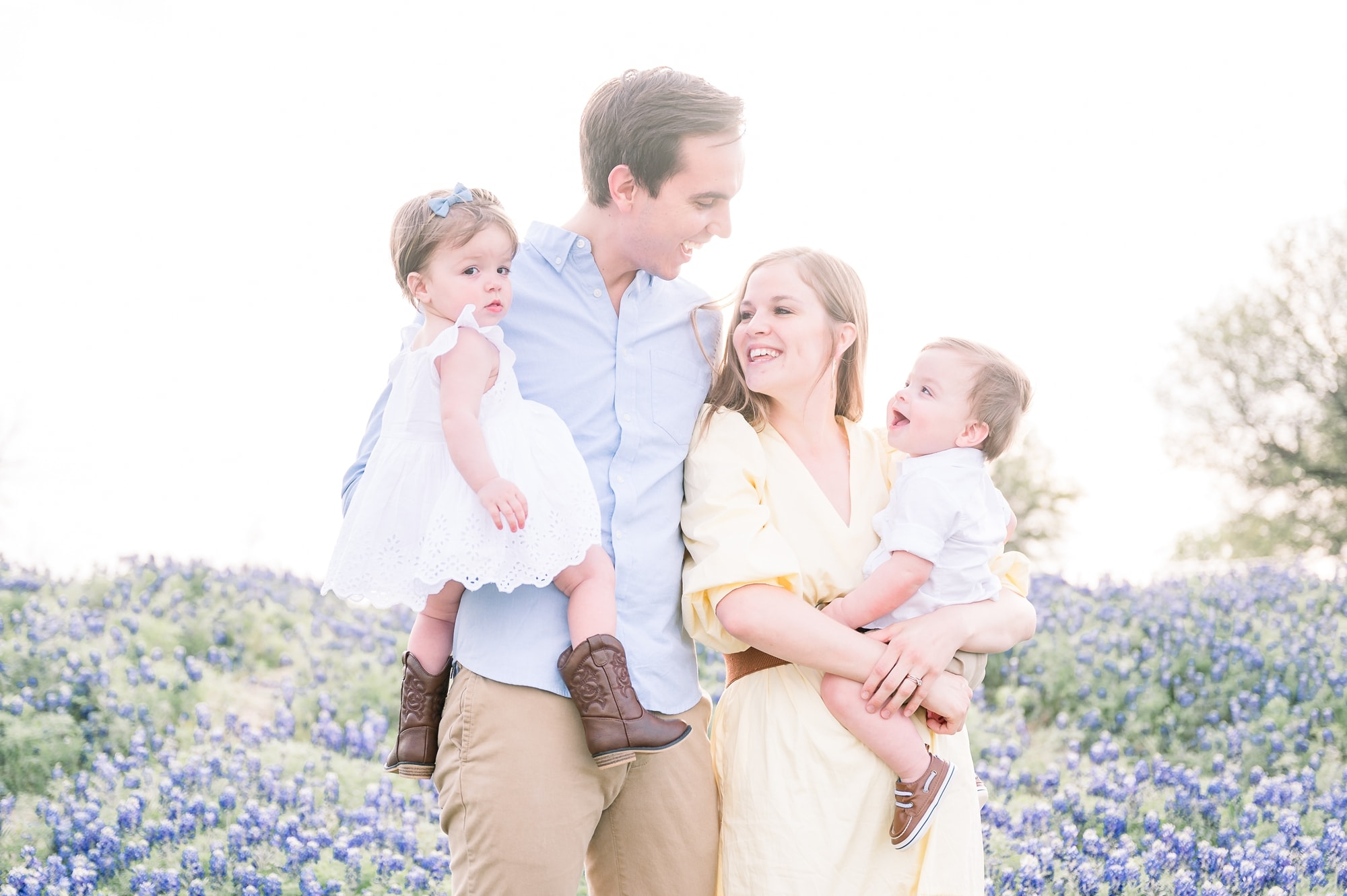 Family of four standing in field of bluebonnets. Photo by Aimee Hamilton Photography.