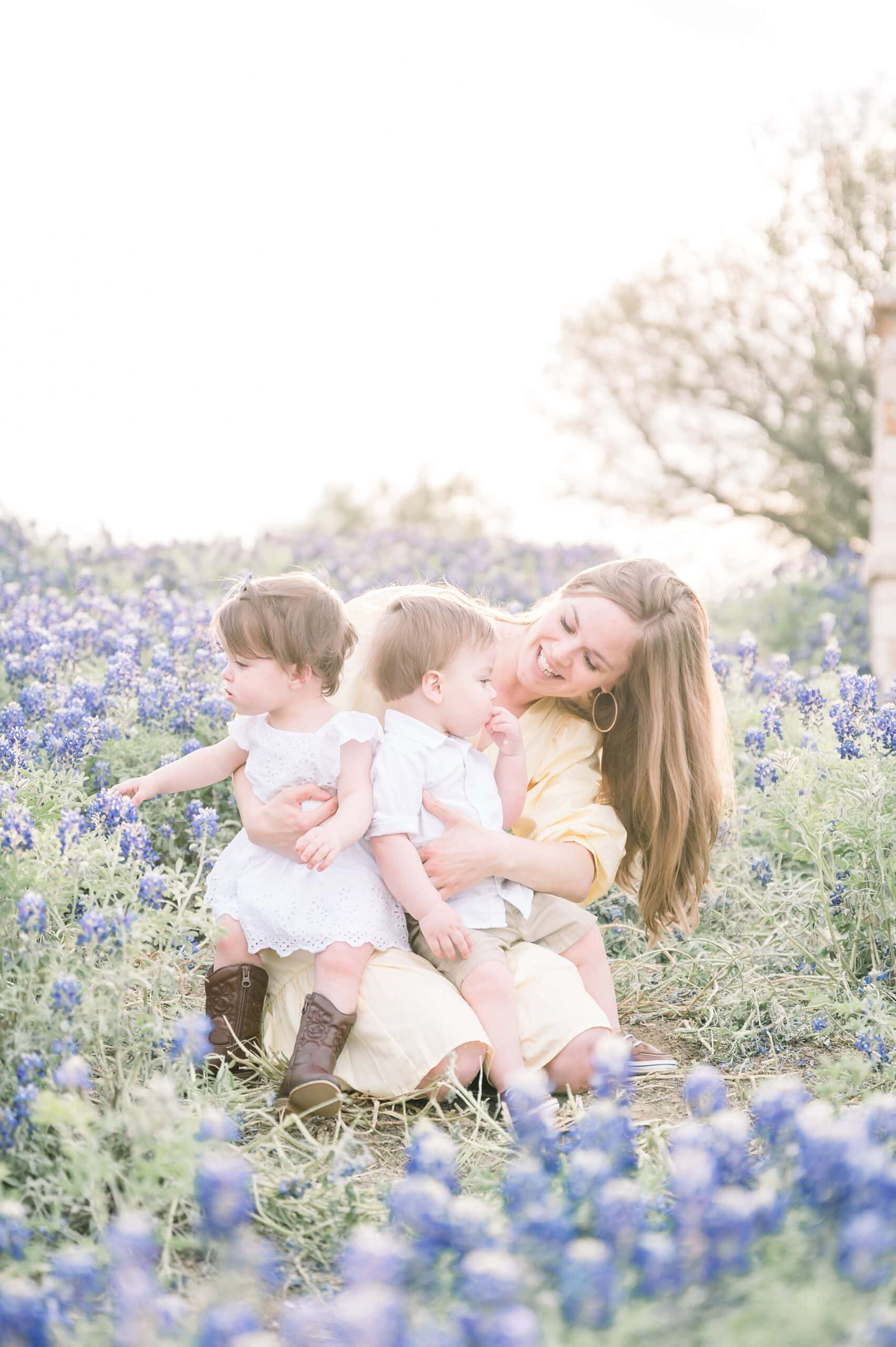 Mom cuddling with twins on sunny evening surrounded by bluebonnet blooms. Photo by Aimee Hamilton Photography.