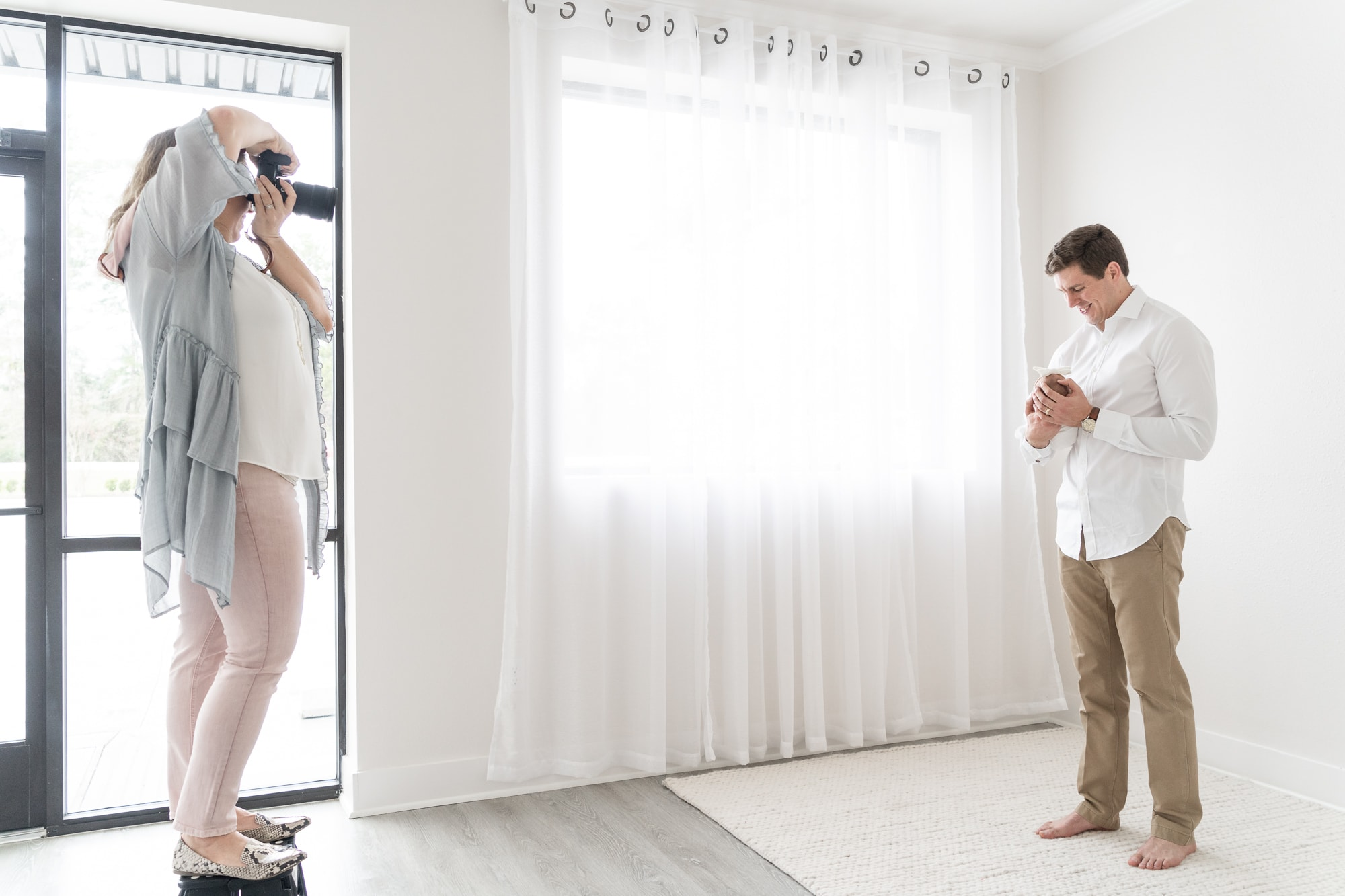 Photographer poses dad in newborn session
