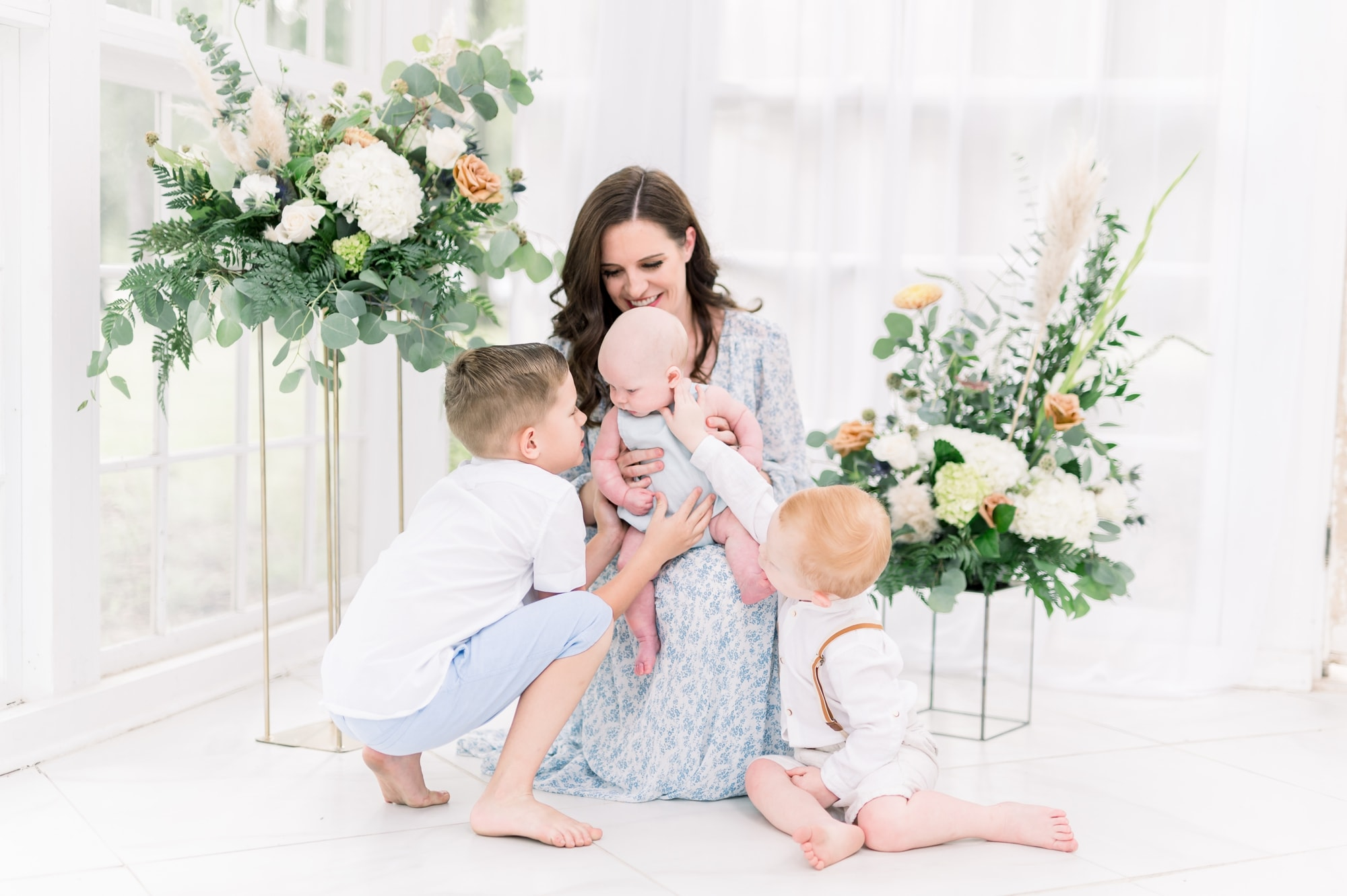 Mom cuddling with three kids in beautiful natural light studio. Photo by Dallas family photographer, Aimee Hamilton Photography.