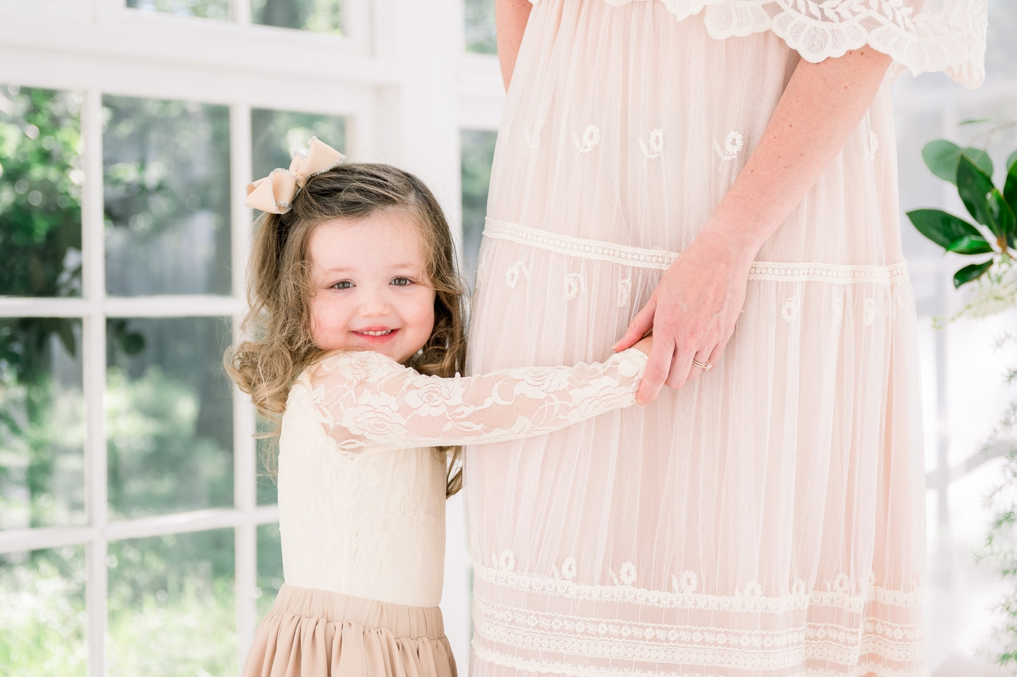 Closeup of little girl holding Mom's hand during motherhood session by Aimee Hamilton Photography.