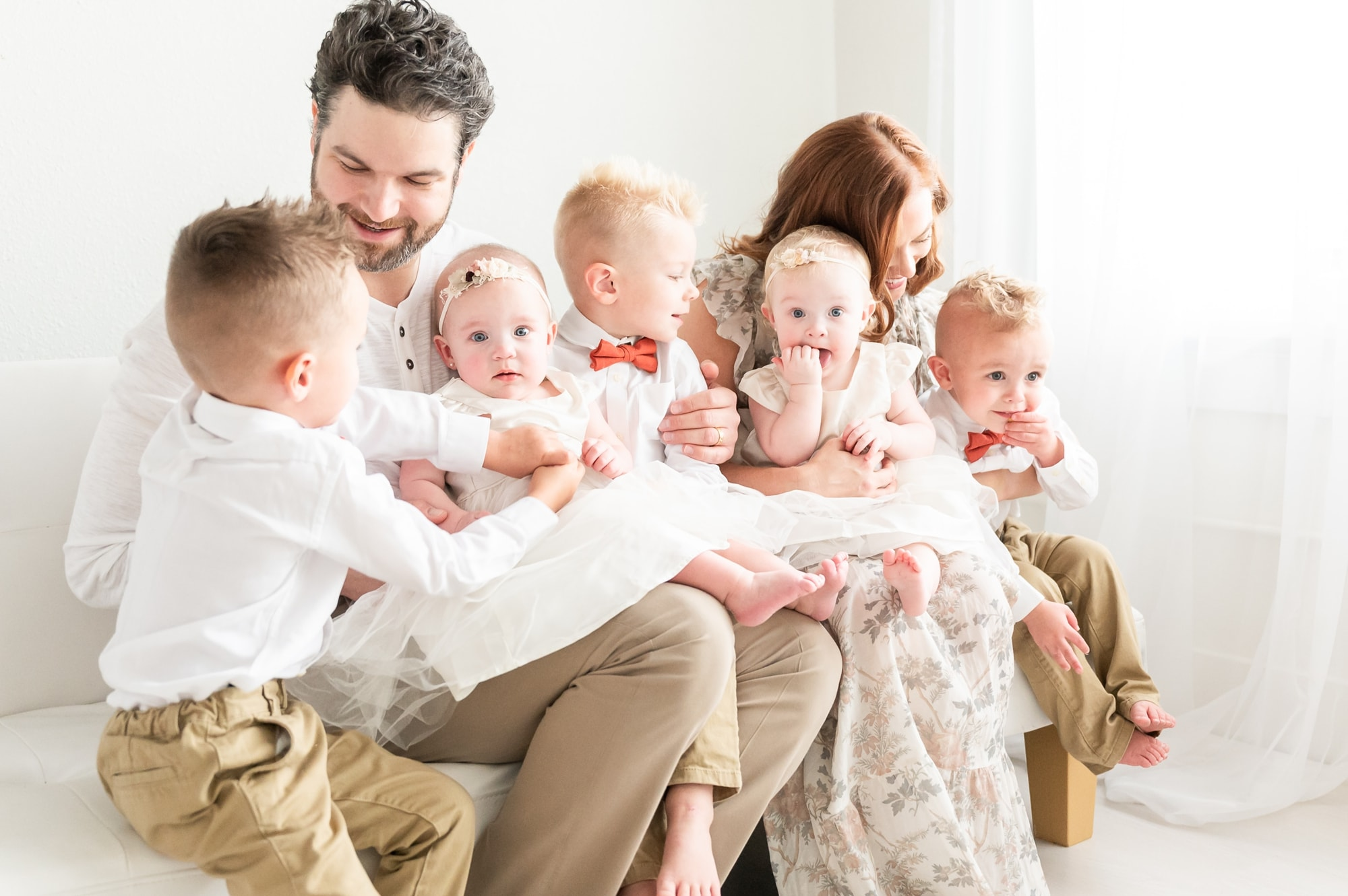 Candid image of parents with five young children in Dallas studio. Photo by Aimee Hamilton Photography.