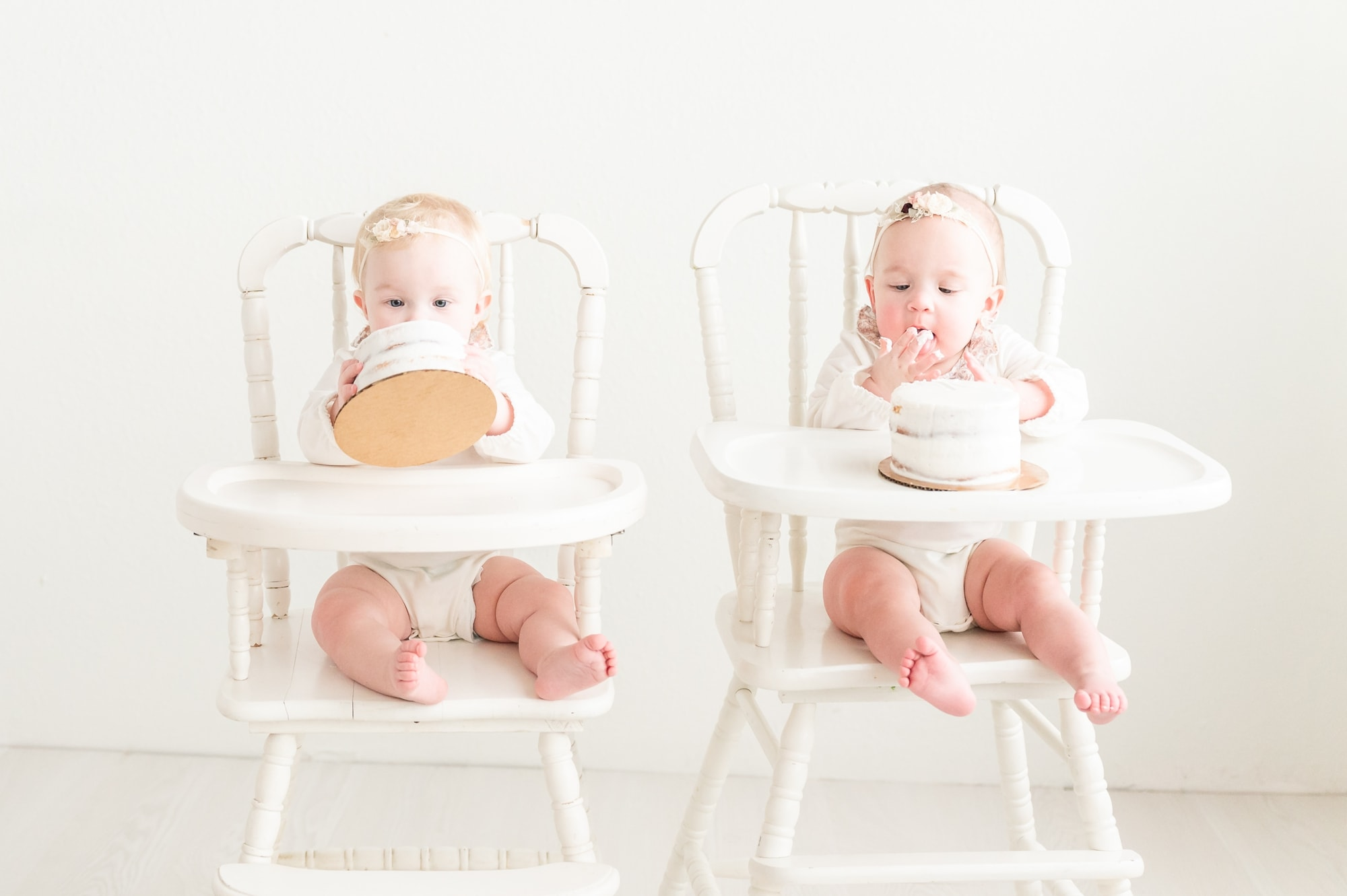 Twins digging into cakes during cake smash session in Dallas studio. Photo by Aimee Hamilton Photography.