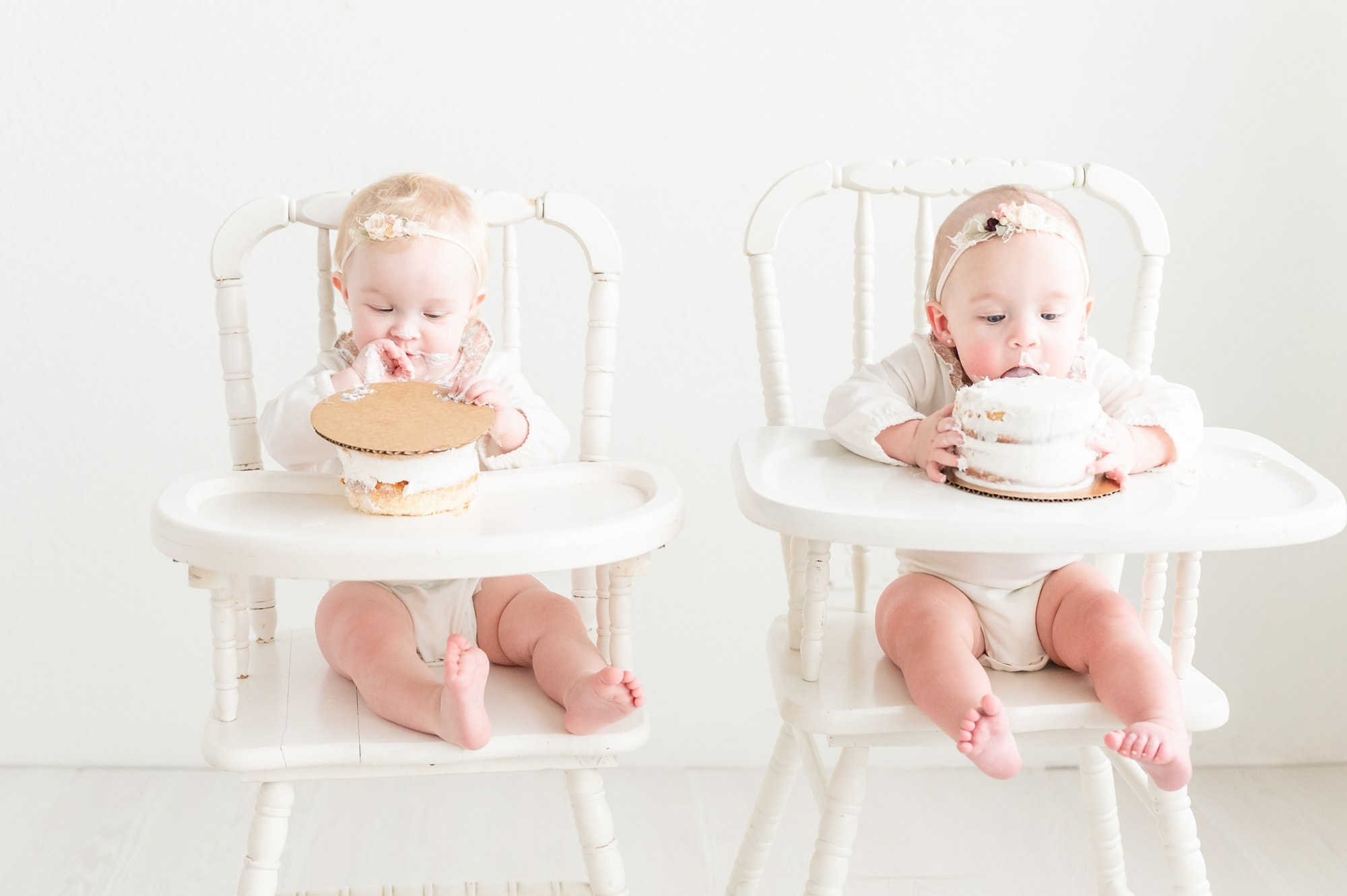 Twins eating cake during first birthday cake smash session in Dallas. Photo by Aimee Hamilton Photography.