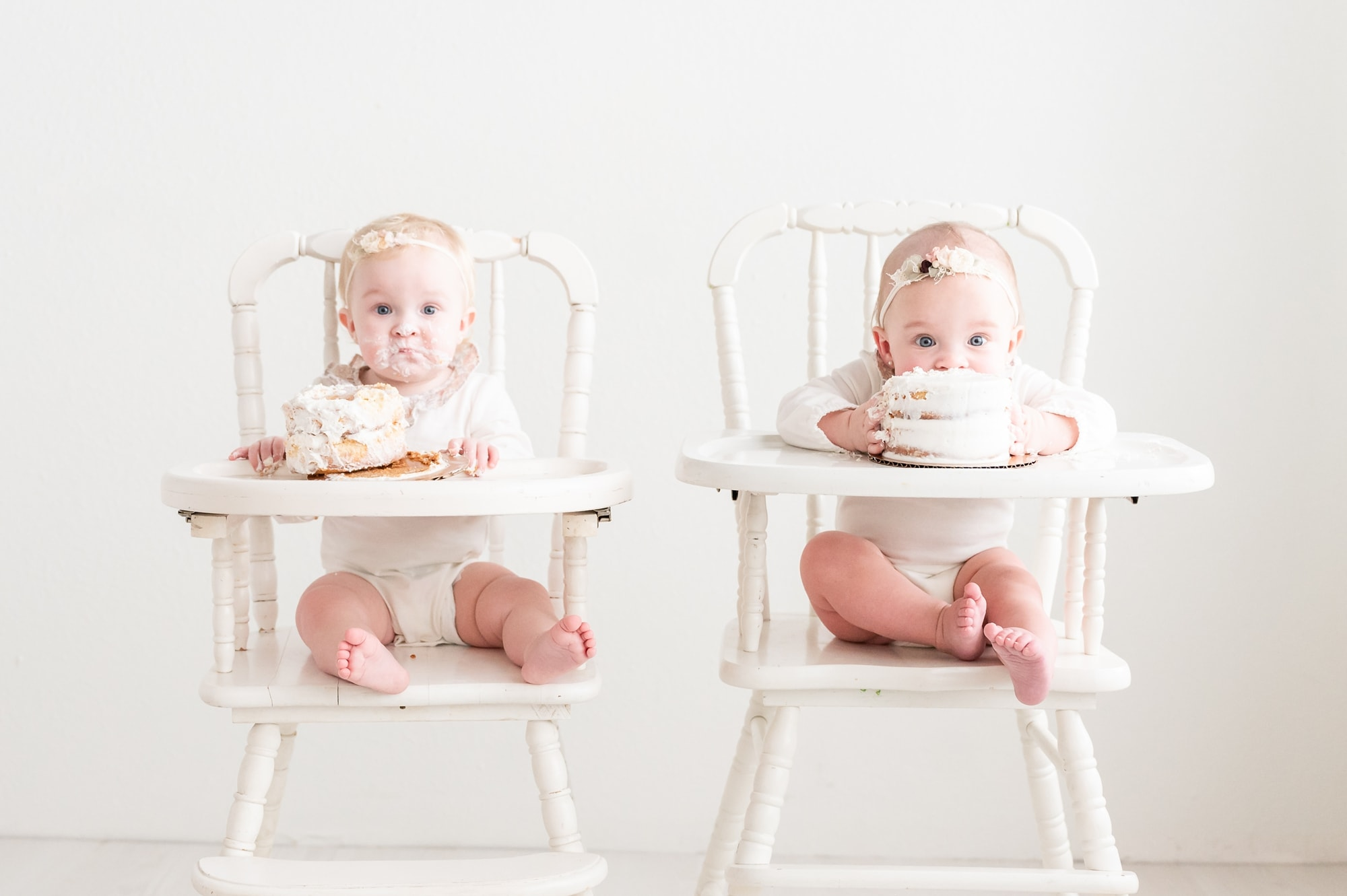 Twins digging into cake smash during first birthday milestone session. Photo by Dallas studio baby photographer, Aimee Hamilton Photography.