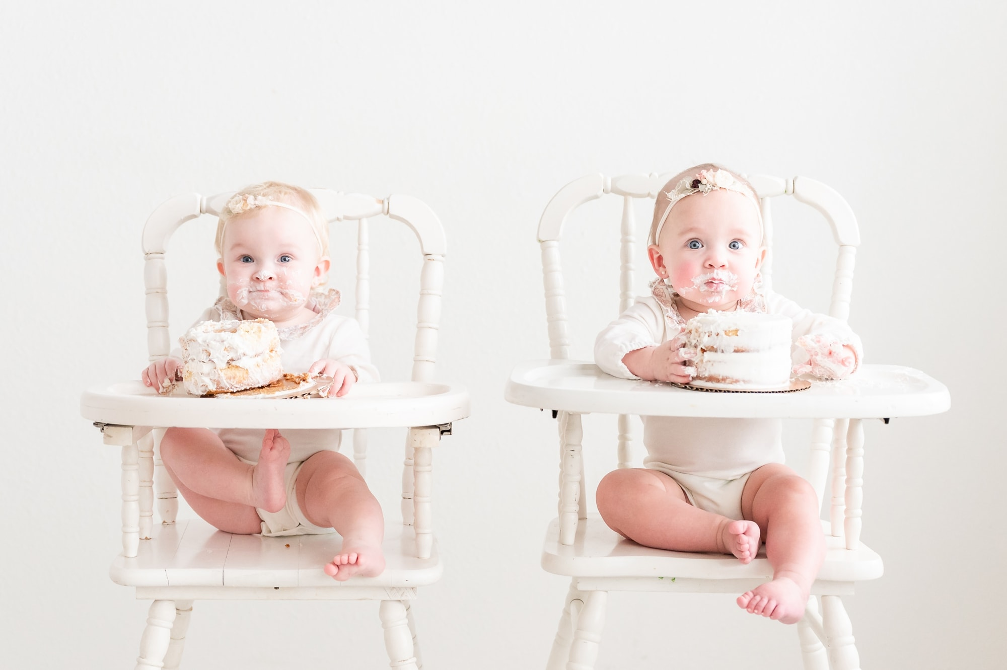 Twin girls sitting in white high chairs for cake smash milestone session. Photo by Dallas studio baby photographer, Aimee Hamilton Photography.