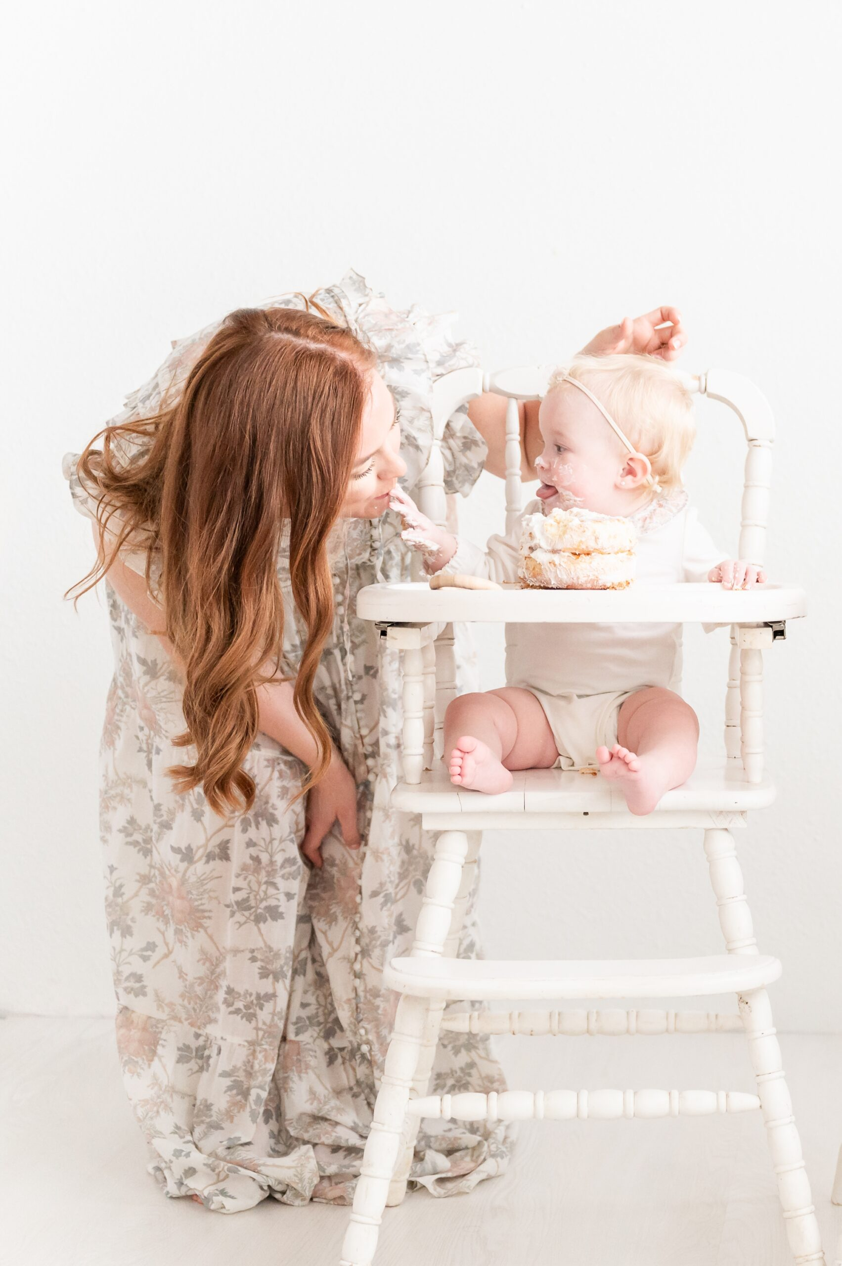 Baby girl feeding Mom cake during first birthday session in Dallas studio. Photo by Aimee Hamilton Photography.