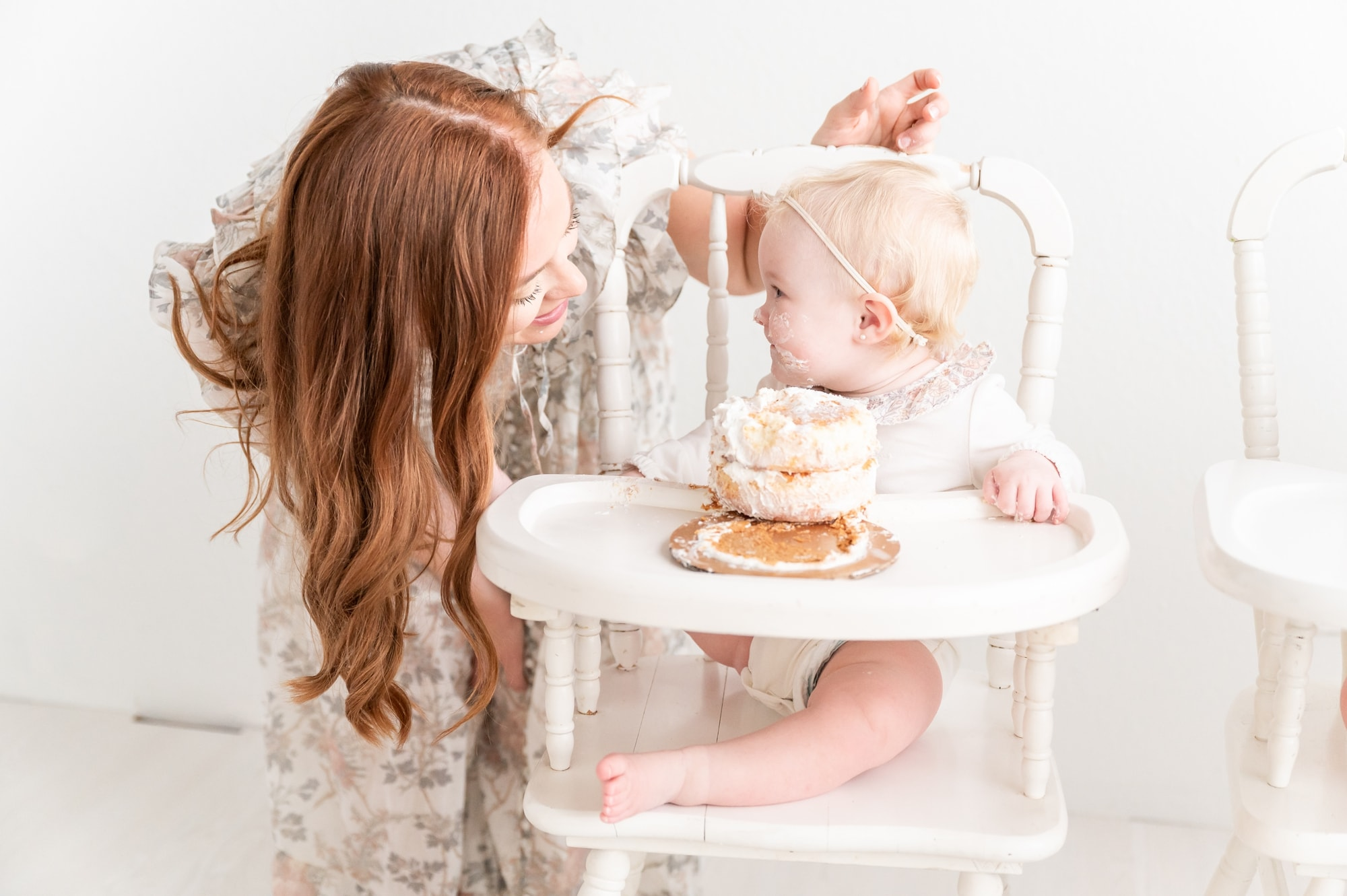 Baby girl looking at Mom while eating cake in white wooden highchair. Photo by Aimee Hamilton Photography.