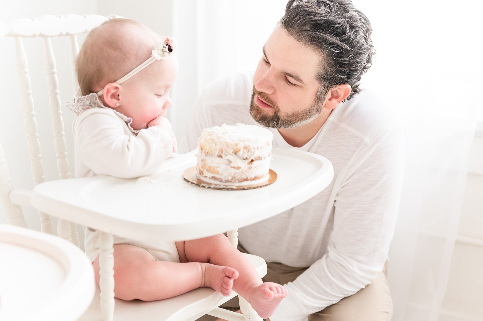 Baby girl easting cake while Dad encourages her during photography session in Dallas studio. Photo by Aimee Hamilton Photography.