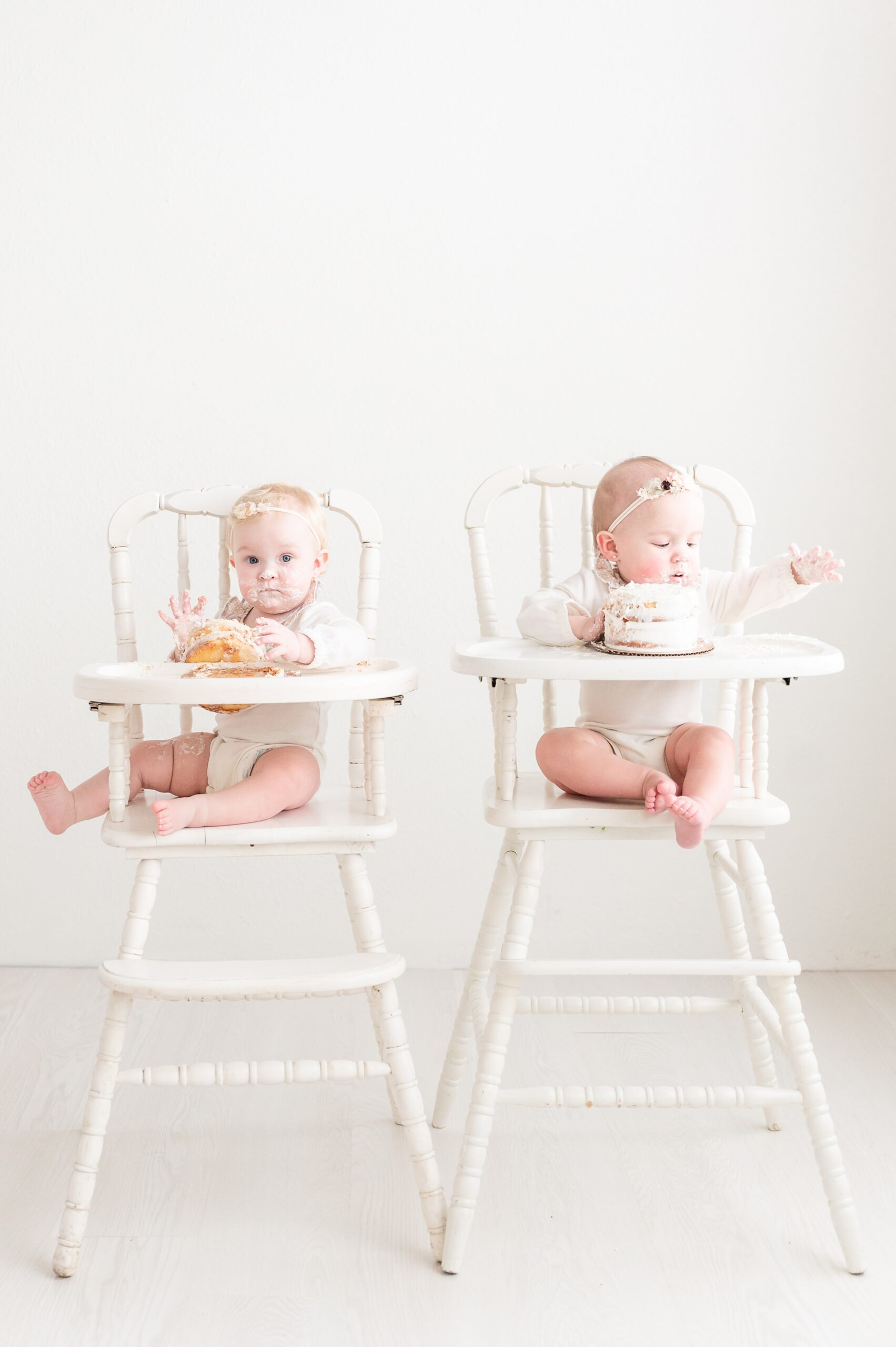 Twin cake smash session with girls in white wooden highchairs. Photo by Dallas studio baby photographer, Aimee Hamilton Photography.