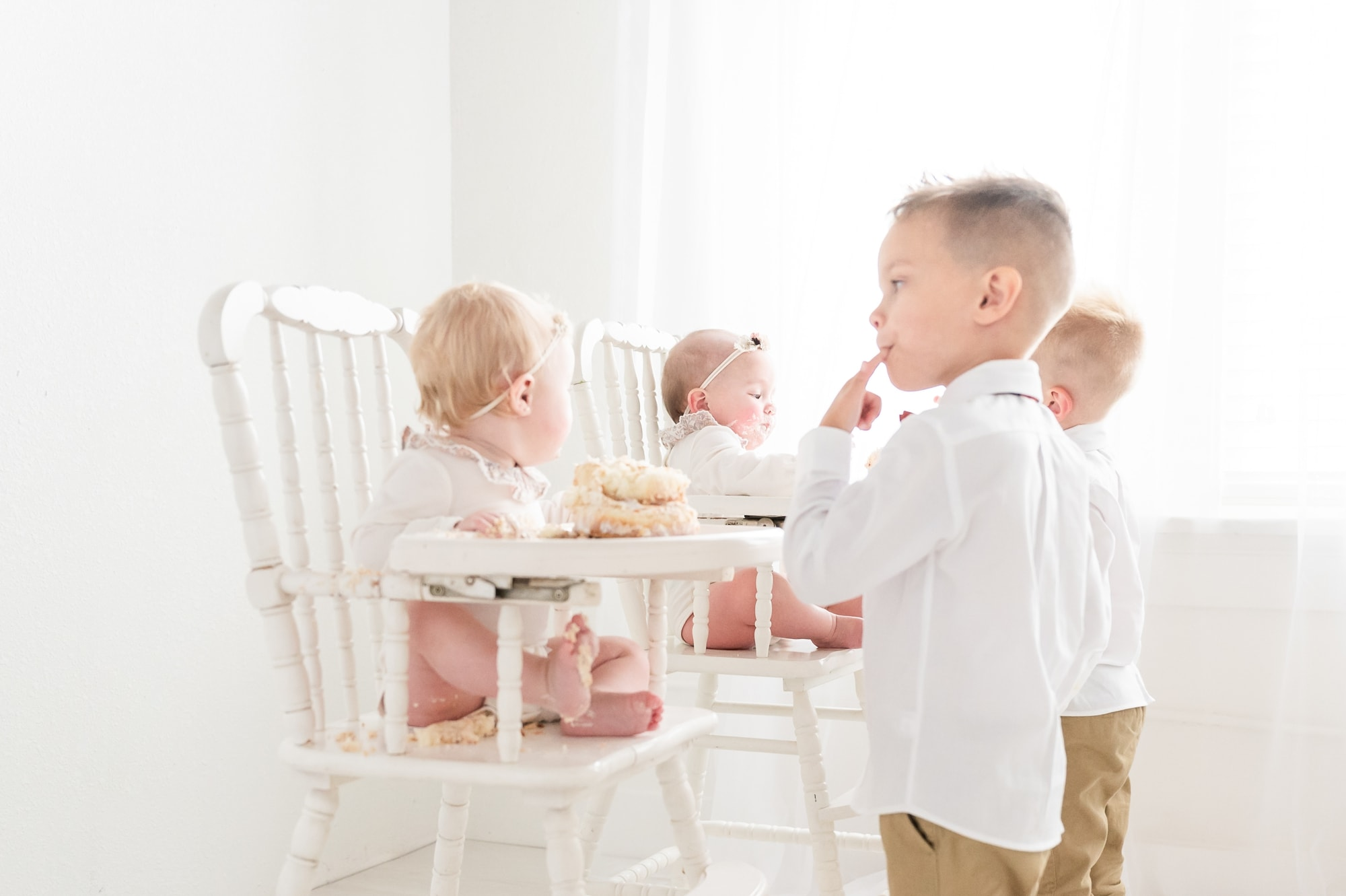 Big brothers tasting baby sisters' cake during first birthday session. Photo by Aimee Hamilton Photography.