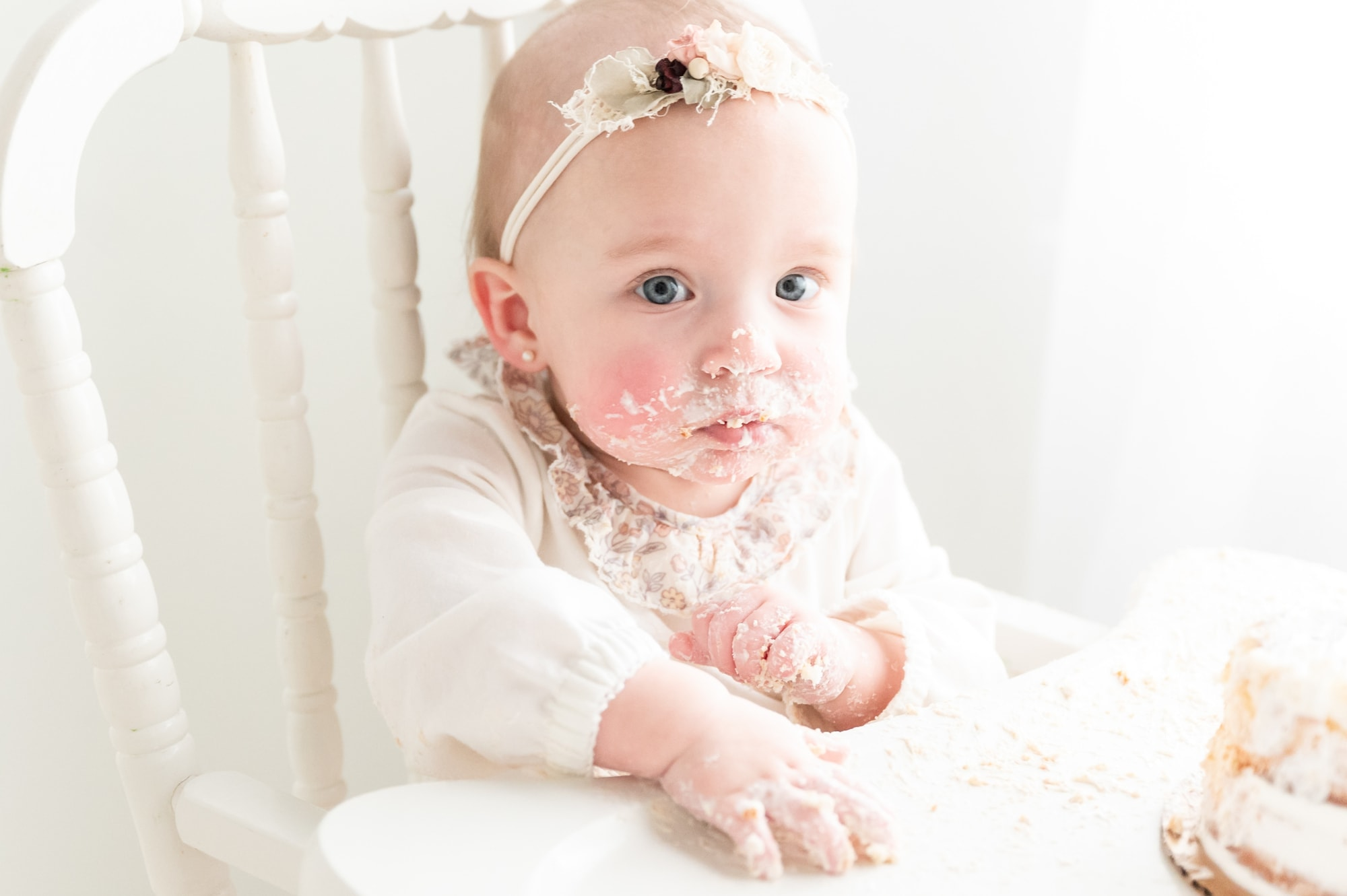 Closeup of baby girl looking at camera during cake smash. Photo by Aimee Hamilton Photography.