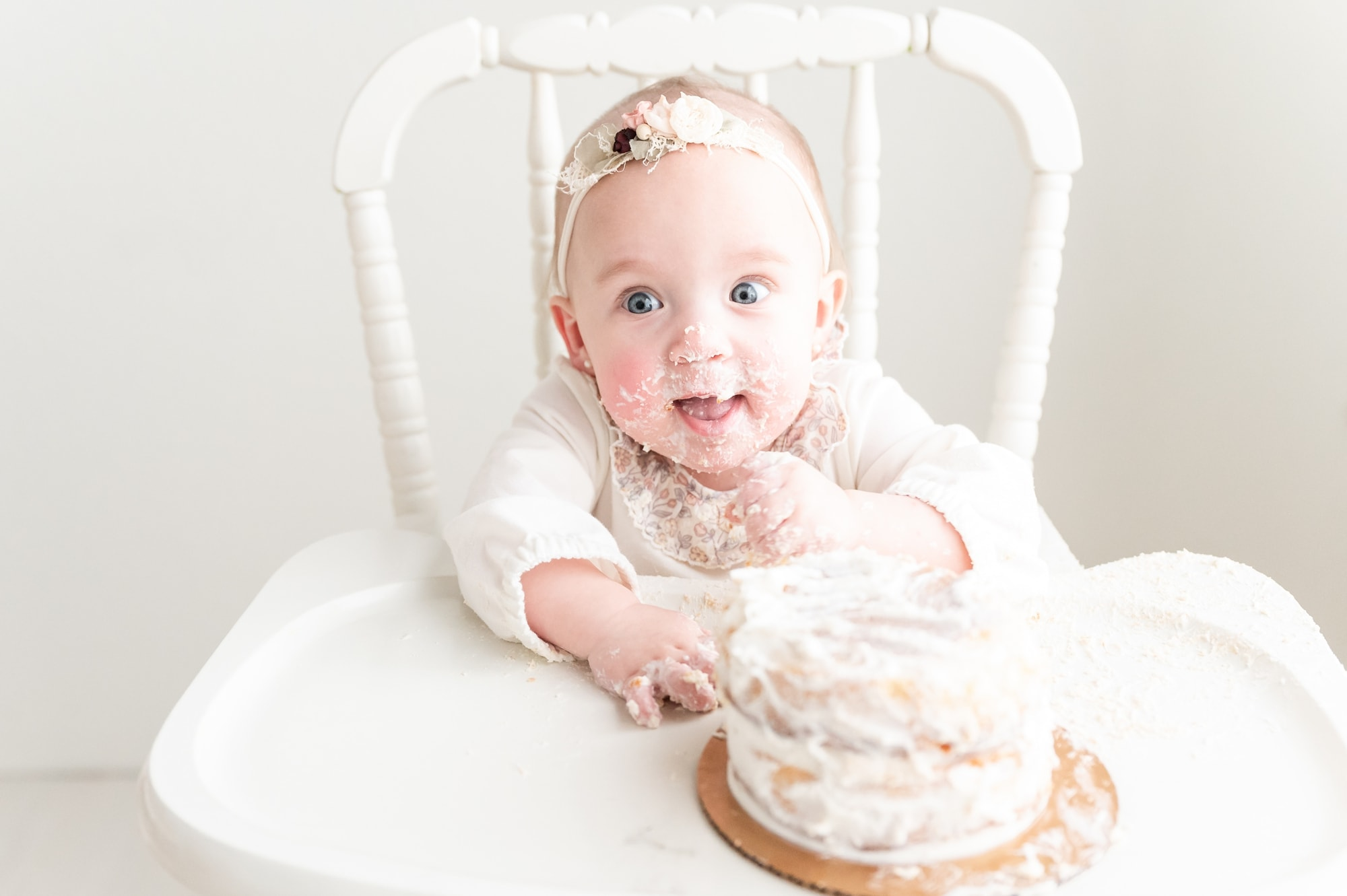 Smiling baby covered in frosting during one year milestone session by Aimee Hamilton Photography.