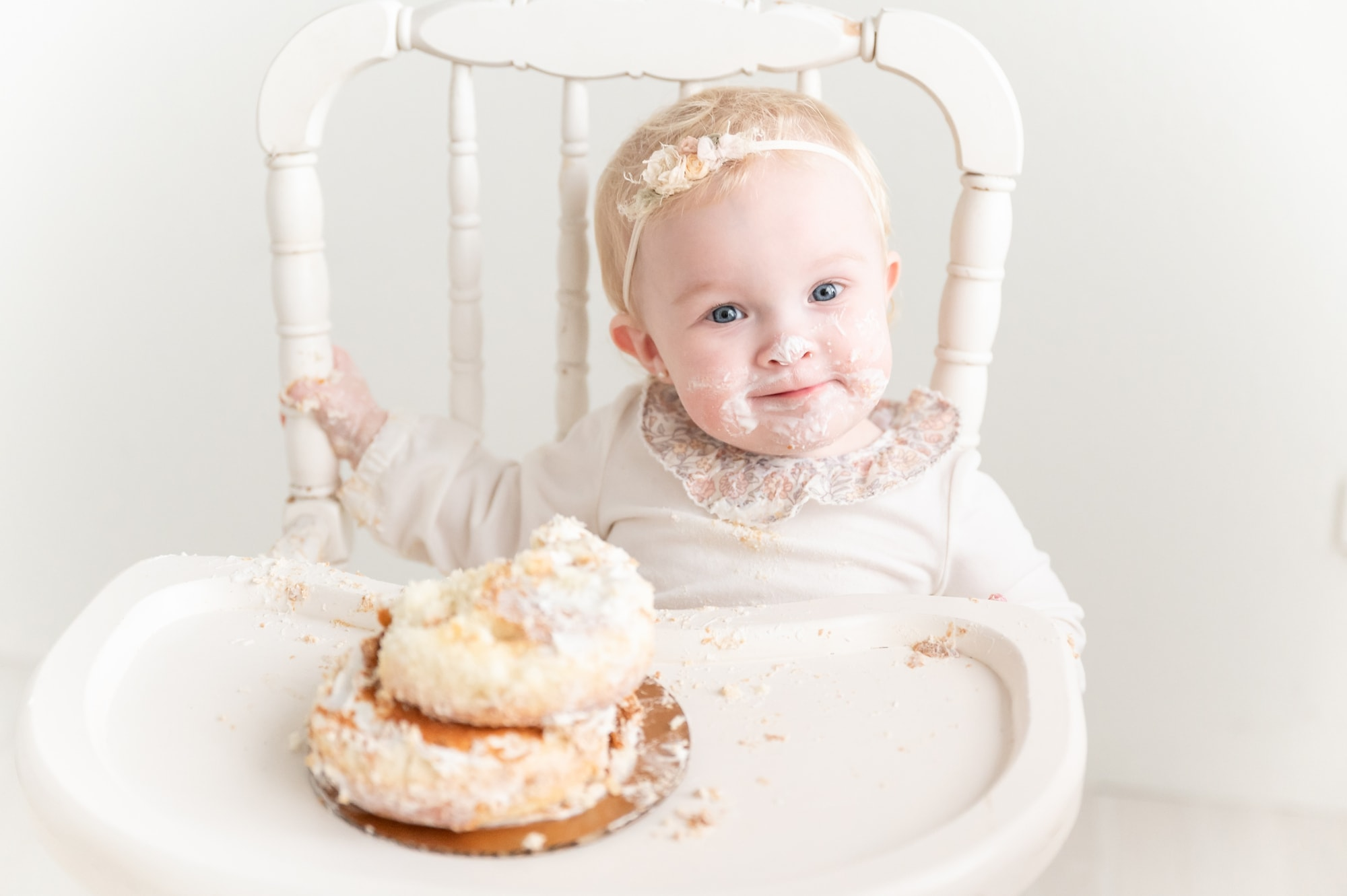 Closeup of little girl wearing floral headband during cake smash. Photo by Aimee Hamilton Photography.