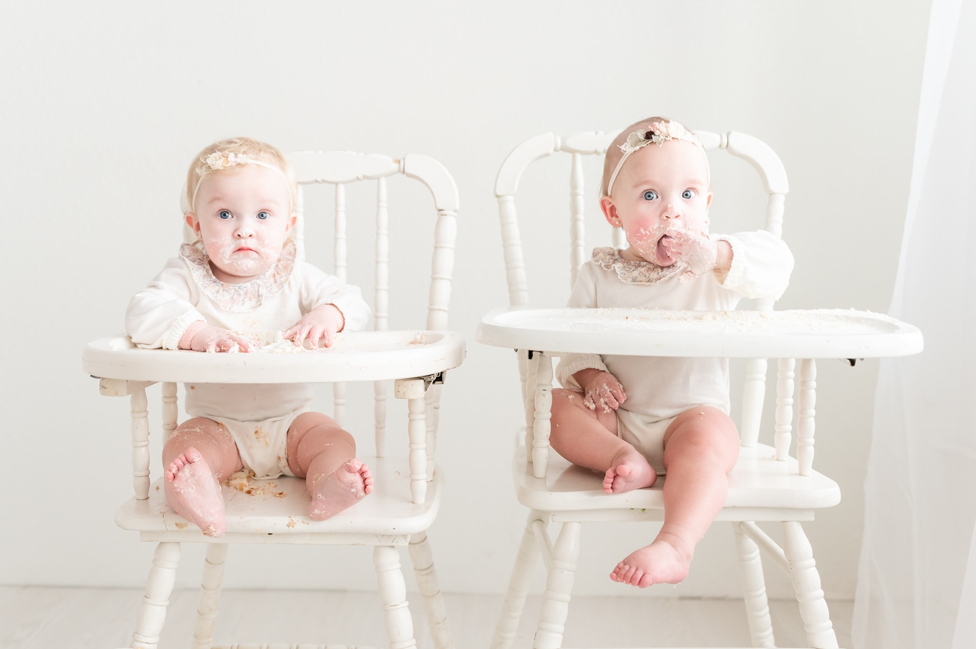 Twin girls covered in frosting at end of first birthday milestone session. Photo by Dallas studio baby photographer, Aimee Hamilton Photography.